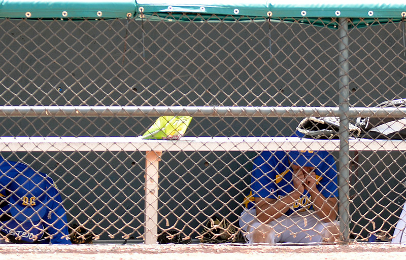 . Dove Creek Kyle Schultz (5) sits dejected in the dugout after their loss to Caliche 17-1 in the Championship game May 15, 2014 at All-Star Park. (Photo by John Leyba/The Denver Post)