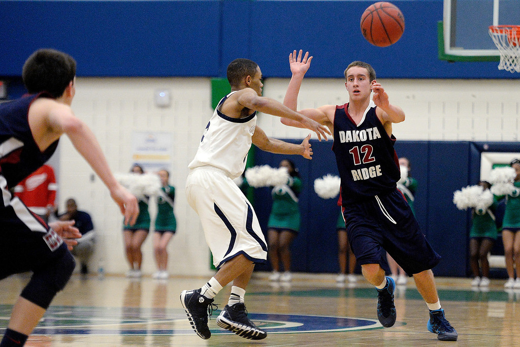 . Jake Flores (12) of the Dakota Ridge Eagles passes around Austin Conway (15) of the Overland Trailblazers during the second half of Overland\'s 67-59 win. (Photo By AAron Ontiveroz/The Denver Post)