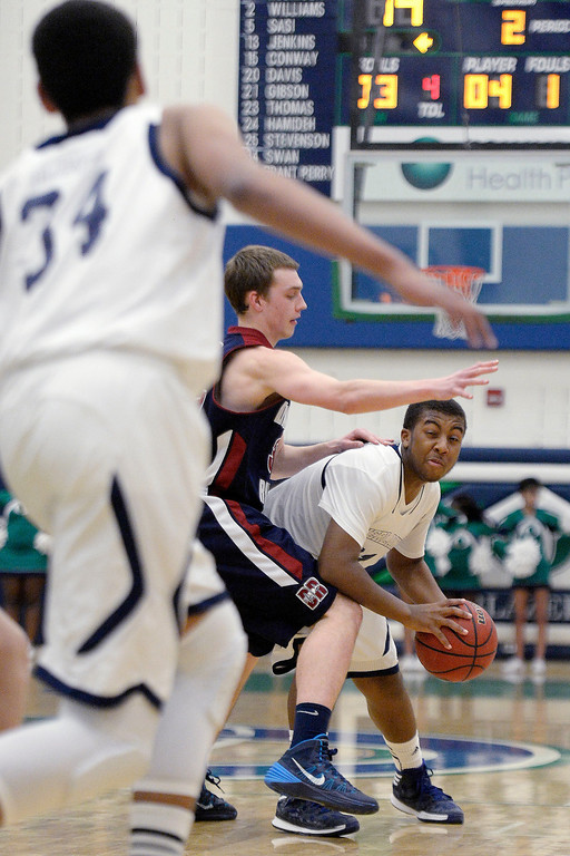 . Reggie Gibson (21) of the Overland Trailblazers looks for an open teammate as Mason Grothuesmann (31) of the Dakota Ridge Eagles guards his tightly during the first half. (Photo By AAron Ontiveroz/The Denver Post)