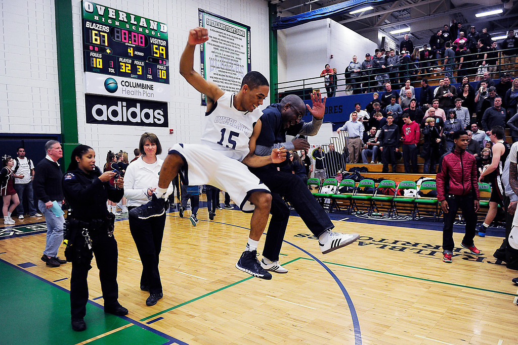 . Austin Conway (15) of the Overland Trailblazers celebrates with principal Leon Lundie after the second half of Overland\'s 67-59 win. (Photo By AAron Ontiveroz/The Denver Post)