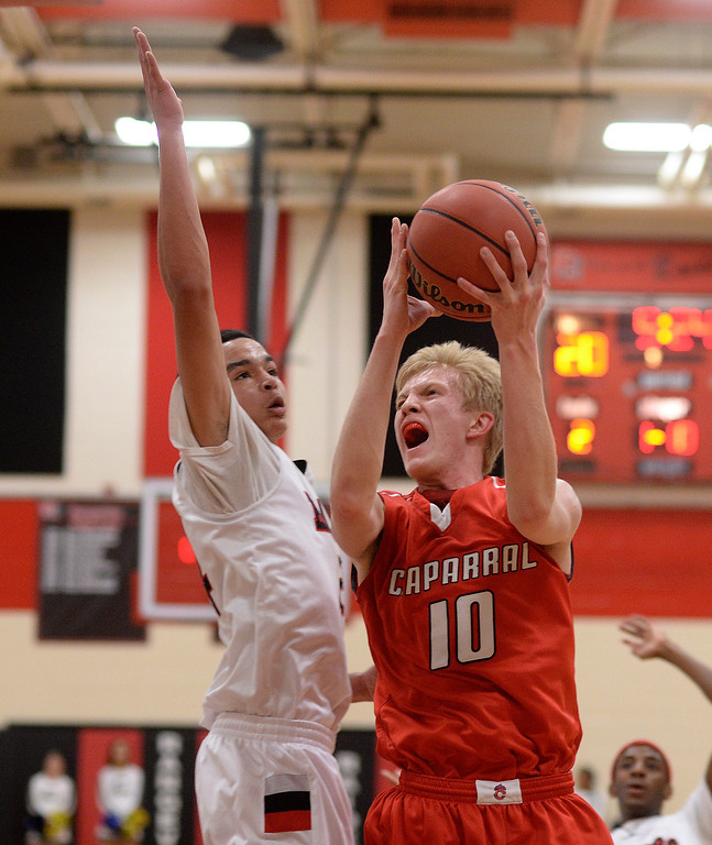 . AURORA, CO. - MARCH 5, 2014: Chaparral junior forward Jake Holtzmann (10) drove to the basket against Rangeview defender Tarren Storey-Way (24) in the first half. The Rangeview High School boy\'s basketball team hosted Chaparral Wednesday night, March 5, 2014. Photo By Karl Gehring/The Denver Post
