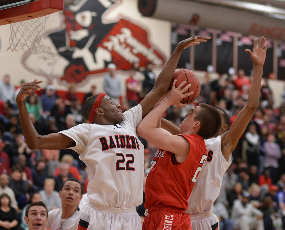 . AURORA, CO. - MARCH 5, 2014: Wolverines guard Chase Coon (23) ran into Raiders defender Jeremiah Paige (22) on the way to the basket in the second half. The Rangeview High School boy\'s basketball team defeated Chaparral 88-85 in the second overtime period Wednesday night, March 5, 2014. Photo By Karl Gehring/The Denver Post