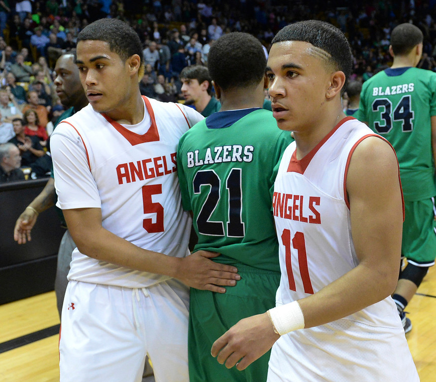 . BOULDER, CO - MARCH 14: Randal Jones (5) and Brian Carey (11) congratulated Overland\'s Reggie Gibson on a great season following the Angel\'s victory. The Denver East High School boy\'s basketball team advanced to the championship game after a 77-65 win over Overland in a 5A semifinal game Friday night, March 14, 2014 in Boulder, Colorado. (Photo by Karl Gehring/The Denver Post)