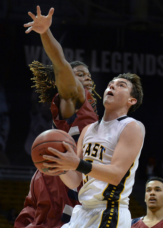 . BOULDER, CO - MARCH 14: Pueblo East guard TJ Gradisar (5) tried to work past Sand Creek defender Langston Bell (21) in the second half. The Pueblo East High School boy\'s basketball team defeated Sand Creek 59-51 in a 4A semifinal game Friday night, March 14, 2014 in Boulder, Colorado. (Photo by Karl Gehring/The Denver Post)