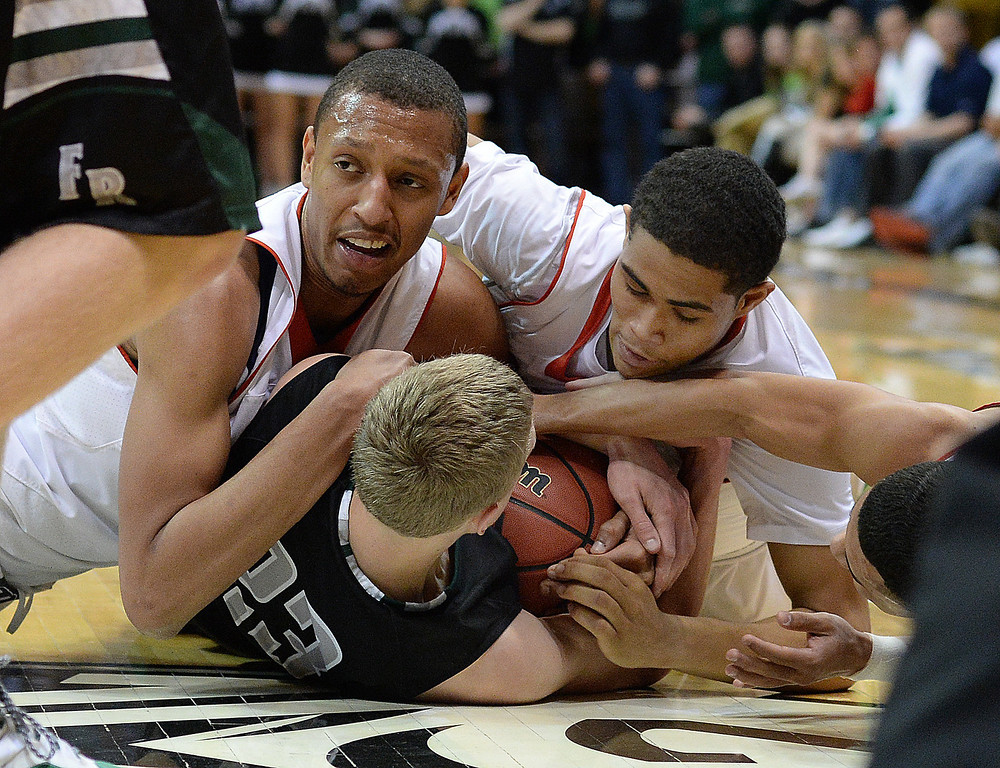 . BOULDER, CO - MARCH15: Denver South forward Tyre Robinson (32) and Brian Carey (11) tried to take the ball from SaberCats\' Alex Semadeni (23) in the first half. The Denver East High School boy\'s basketball team took on Fossil Ridge in the 5A championship game Saturday night, March 15, 2014 in Boulder, Colorado. (Photo by Karl Gehring/The Denver Post)