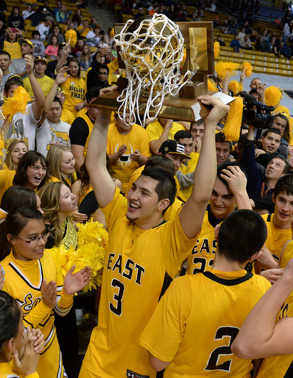 . BOULDER, CO - MARCH15: Pueblo East senior Alex Jara paraded the trophy through the mob of students at the end of the game. The Pueblo East High School boy\'s basketball team took the 4A state title with a 58-51 win over Denver South in the championship game Saturday night, March 15, 2014 in Boulder, Colorado. (Photo by Karl Gehring/The Denver Post)