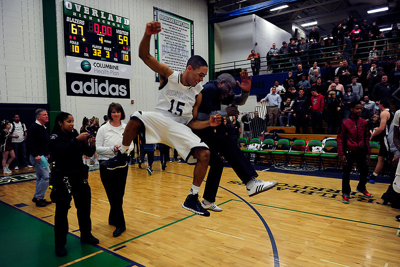 . Austin Conway (15) of the Overland Trailblazers celebrates with principal Leon Lundie after the second half of Overland\'s 67-59 win. CHSAA boys basketball on Wednesday, March 5, 2014. (Photo By AAron Ontiveroz/The Denver Post)