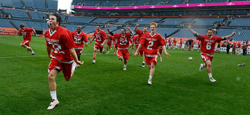 . The Regis Lacrosse team runs to celebrate with  their fan after winning the Colorado State 5A boys lacrosse championship at Sports Authority Field at Mile High Saturday evening, May 17, 2014. Regis defeated Cherry Creek, 14-7.  (Photo By Andy Cross / The Denver Post)