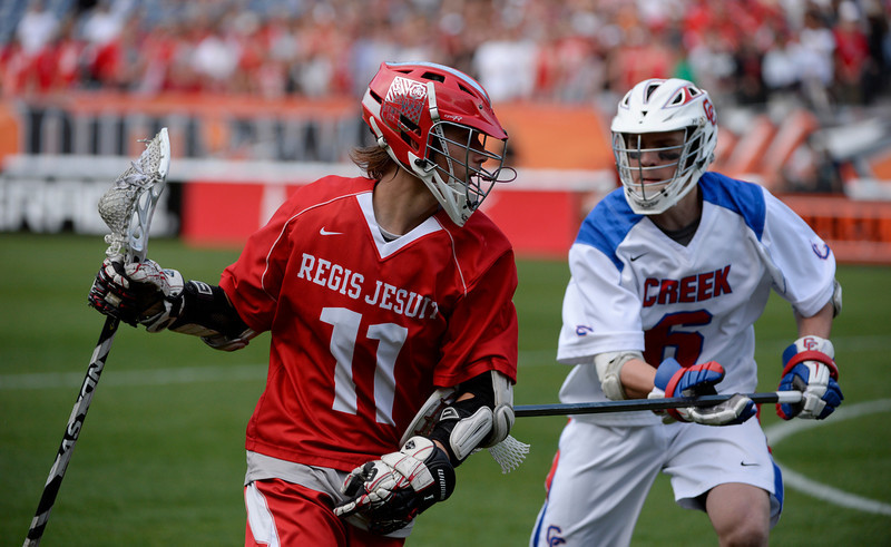 . Regis attacker, Truett Davis, left, looks for room against Cherry Creek defender, James McKenna, right, during the Colorado State 5A boys lacrosse Championship at Sports Authority Field at Mile High Saturday evening, May 17, 2014. Regis won 14-7. (Photo By Andy Cross / The Denver Post)