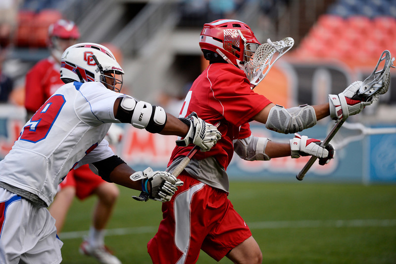 . Regis midfielder, Aaron Horvat, right, heads around the defense of Steve O\'Malley, left, during the first half of the Colorado State 5A boys lacrosse Championship at Sports Authority Field at Mile High Saturday evening, May 17, 2014. (Photo By Andy Cross / The Denver Post)