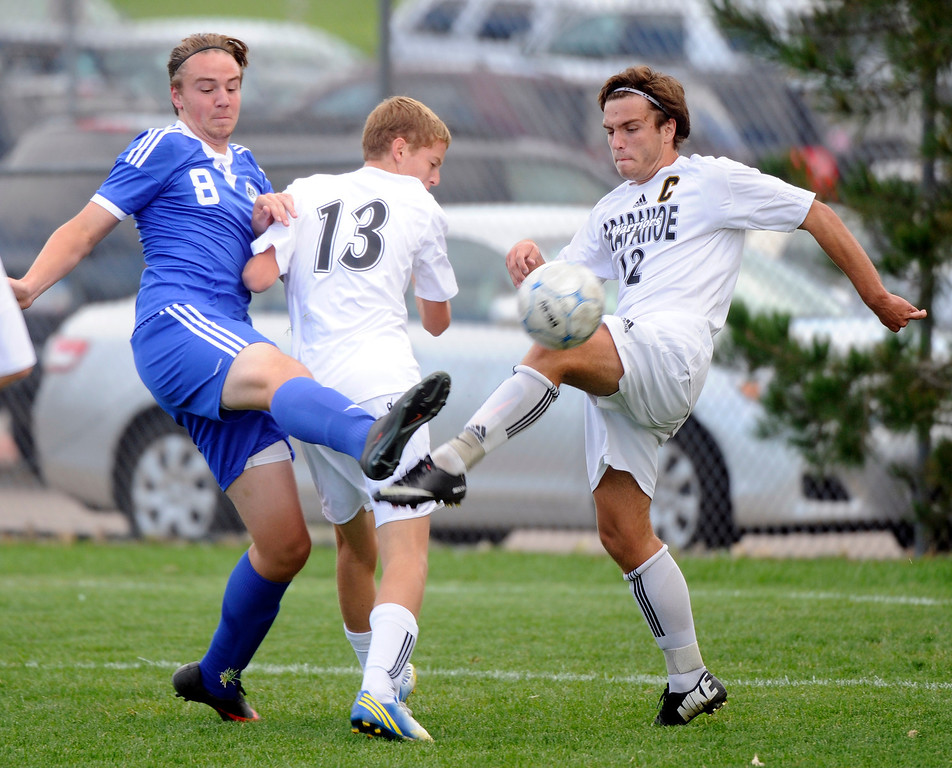 . Grandview senior striker Alex Simpson (8) tries to get a shot past Arapahoe defenders Mitchell Fisher (13) and Noah Graham (12) in the first half. The Grandview High School boy\'s soccer team defeated Arapahoe 2-0 Thursday evening, September 19, 2013.  Photo By Karl Gehring/The Denver Post