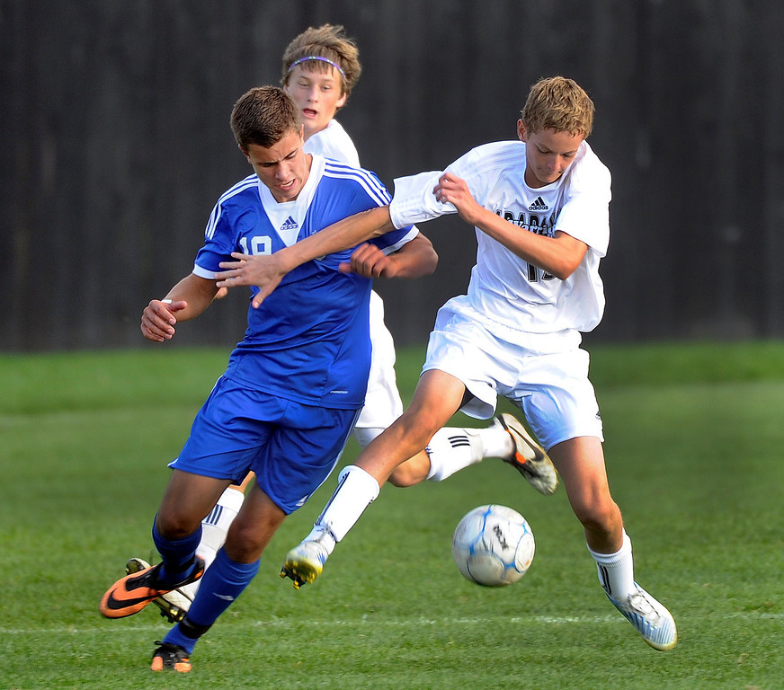 . LITTLETON, CO. - SEPTEMBER 19: Arapahoe defender Mitchell Fisher (13) tried to slow down Grandview striker Rhys De Sota (19) in the second half. The Grandview High School boy\'s soccer team defeated Arapahoe 2-0 Thursday evening, September 19, 2013.  Photo By Karl Gehring/The Denver Post