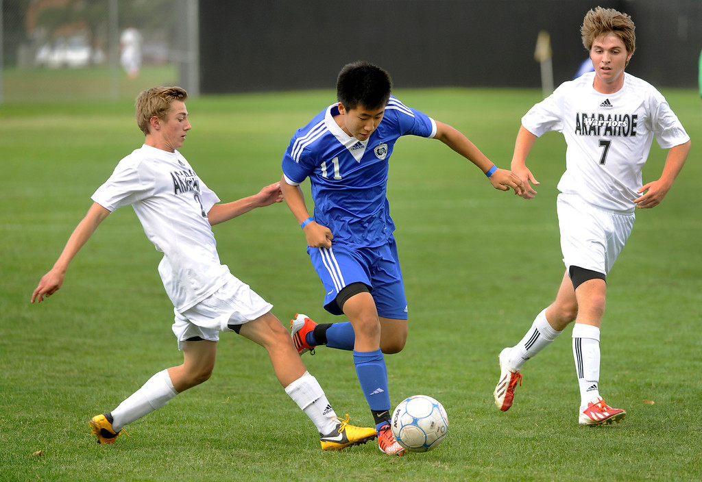 . LITTLETON, CO. - SEPTEMBER 19: Grandview junior midfielder David Kim (11) moved the ball between Arapahoe\'s Chase Brasher  (2) and Jack Ryan (7) in the first half. The Grandview High School boy\'s soccer team defeated Arapahoe 2-0 Thursday evening, September 19, 2013.  Photo By Karl Gehring/The Denver Post