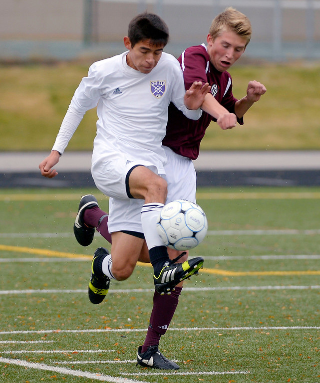 . North High School\'s Devon Soto (13) battles for the ball with Golden\'s Adam Elliot (17) during the first half of play. Denver North High soccer team takes the second round with a win over the Golden Demons October 29, 2013 at North High. The goal was scored by Danny Bautista late in the second half. (Photo by John Leyba/The Denver Post)