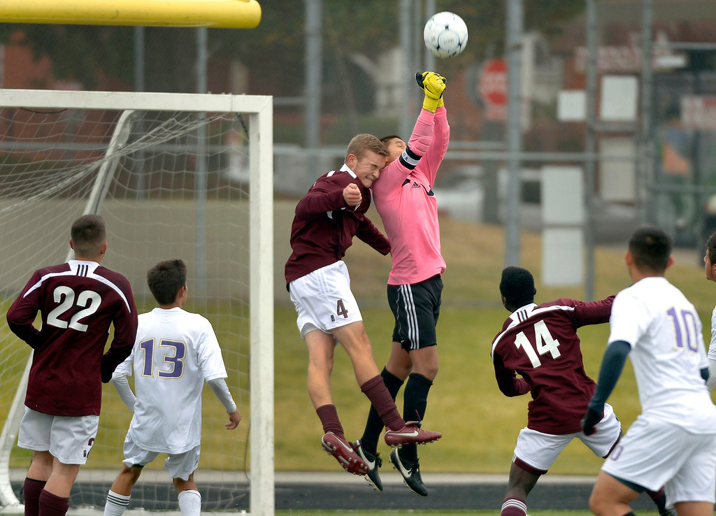 . North goalkeeper Jorge Vega (1) punches the ball away as Golden\'s Jack Breer (4) tries for the header during the second half. Denver North High soccer team takes the second round with a win over Golden Demons October 29, 2013 at North High.  (Photo by John Leyba/The Denver Post)
