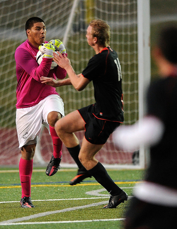 . East forward Harald Saeterdal (16) challenged Rangeview goalkeeper Edward Zuniga as he made a save in the second half.   Photo By Karl Gehring/The Denver Post