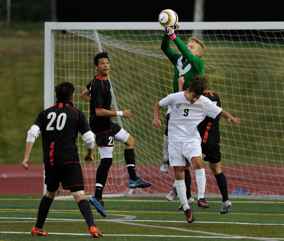 . East goalkeeper Will Palmquist punched the ball away from Raiders\' forward Fernando Chavez (9) in the first half.    Photo By Karl Gehring/The Denver Post