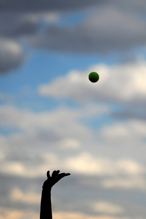 . A player throws the ball up in the air during his serve during the meet between Cherry Creek and Fairview high schools.   (Photo By Erin Hull/The Denver Post)
