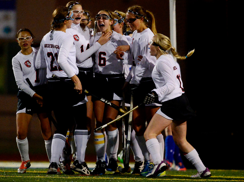 . Colorado Academy\'s players celebrate a goal by Julia Murphy as Cherry Creek\'s Blair Sisk walks back into position during the CHSAA state field hockey championship. Colorado Academy (17-0) capped a perfect season at All-City Stadium. (Photo by AAron Ontiveroz/The Denver Post)