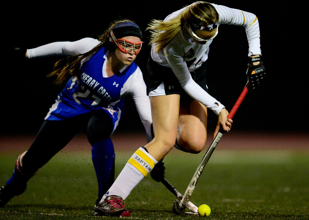 . Colorado Academy\'s Nellie Turnage controls the ball as Cherry Creek\'s Clare Kavanagh defends during the CHSAA state field hockey championship. Colorado Academy (17-0) capped a perfect season at All-City Stadium. (Photo by AAron Ontiveroz/The Denver Post)