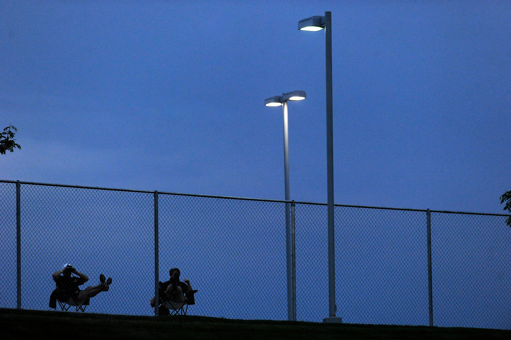 . THORNTON, CO. - AUGUST 29:  Spectators watched the game through a chain link fence Thursday night. The Horizon High School football team hosted Grandview Thursday night, August 29, 2013.  Photo By Karl Gehring/The Denver Post