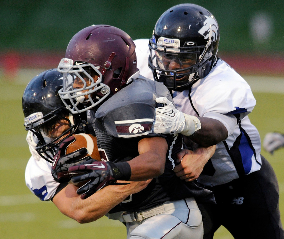. Horizon running back Jordan Iacovetta (15) was dragged down by a pair of Grandview defenders in the first half. The Horizon High School football team hosted Grandview Thursday night, August 29, 2013.  Photo By Karl Gehring/The Denver Post
