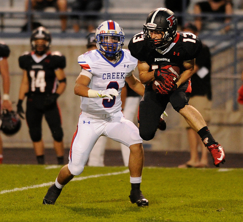 . ARVADA, CO. - SEPTEMBER 6: Pomona defensive back Taylor Thomas (13) picked off a pass intended for Bruins\' receiver Joseph Parker in the second quarter. The Pomona High School football team hosted Cherry Creek Friday night, September 6, 2013. Photo By Karl Gehring/The Denver Post