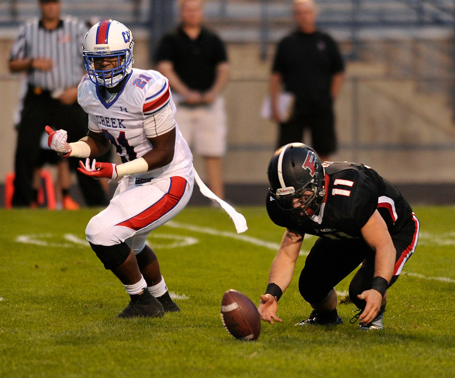 . ARVADA, CO. - SEPTEMBER 6: Pomona linebacker Gus Karr (11) scooped up a fumble in the second quarter. The Pomona High School football team hosted Cherry Creek Friday night, September 6, 2013. Photo By Karl Gehring/The Denver Post