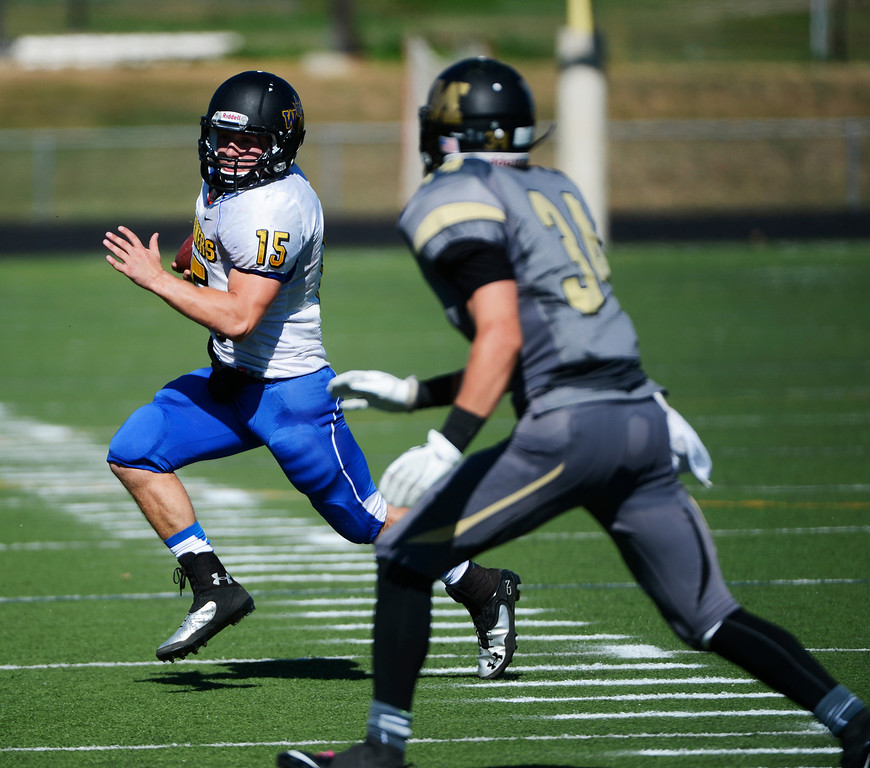 . LAFAYETTE, CO - SEPTEMBER 07: Wheat Ridge QB, Tanner Weakland, left, looks for running room on a keeper against Kidd Sole, Monarch High, in the first quarter of play at the Howard Spangenberg Field in Lafayette Colorado, Saturday morning, September 07, 2013. (Photo By Andy Cross/The Denver Post)