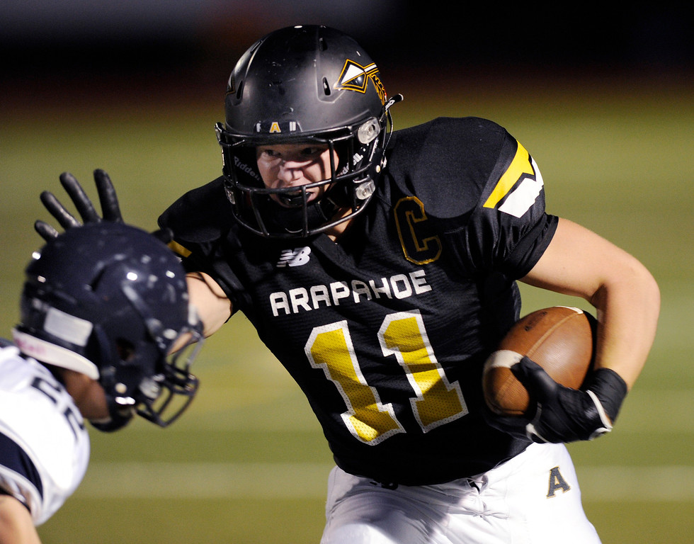 . Arapahoe receiver Ethan Brunhofer (11) tried to fend off Columbine defender Emery Taylor (22) in the first quarter. The Arapahoe High School football team hosted Columbine at the Littleton Public Schools District Stadium Thursday night, September 26, 2013. Photo By Karl Gehring/The Denver Post