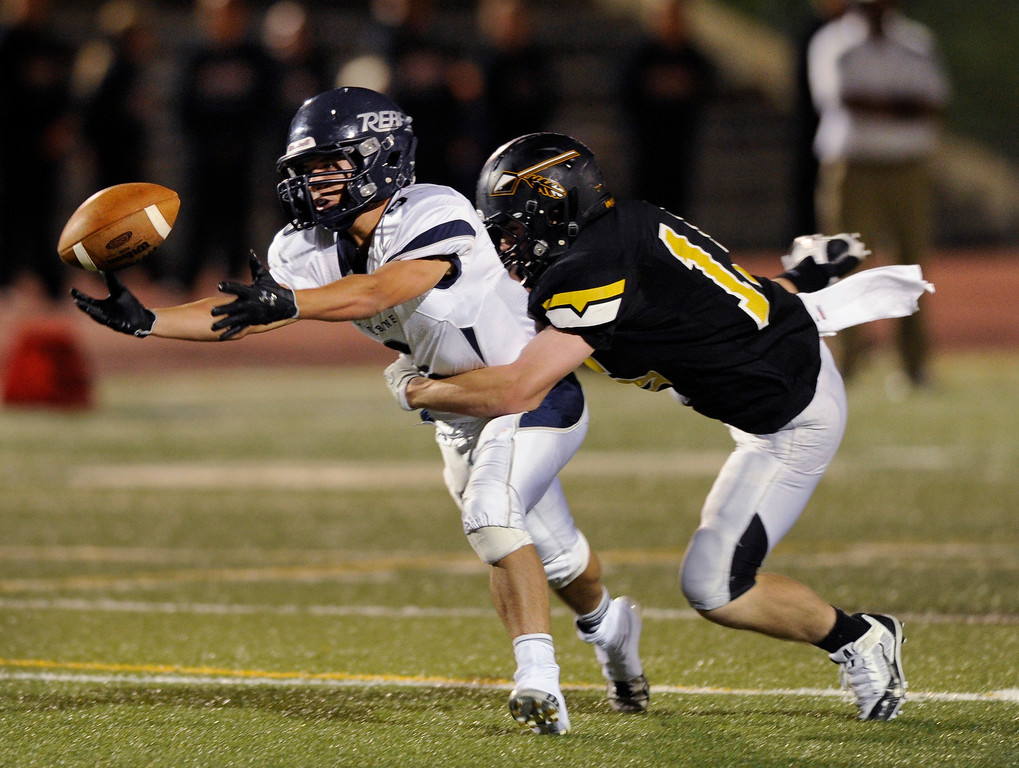 . Warriors defensive back Cooper Glass (15) helped break up a pass intended for Columbine receiver Austin Norton (6) in the second half. The Arapahoe High School football team defeated Columbine 49-28 at the Littleton Public Schools District Stadium Thursday night, September 26, 2013. Photo By Karl Gehring/The Denver Post