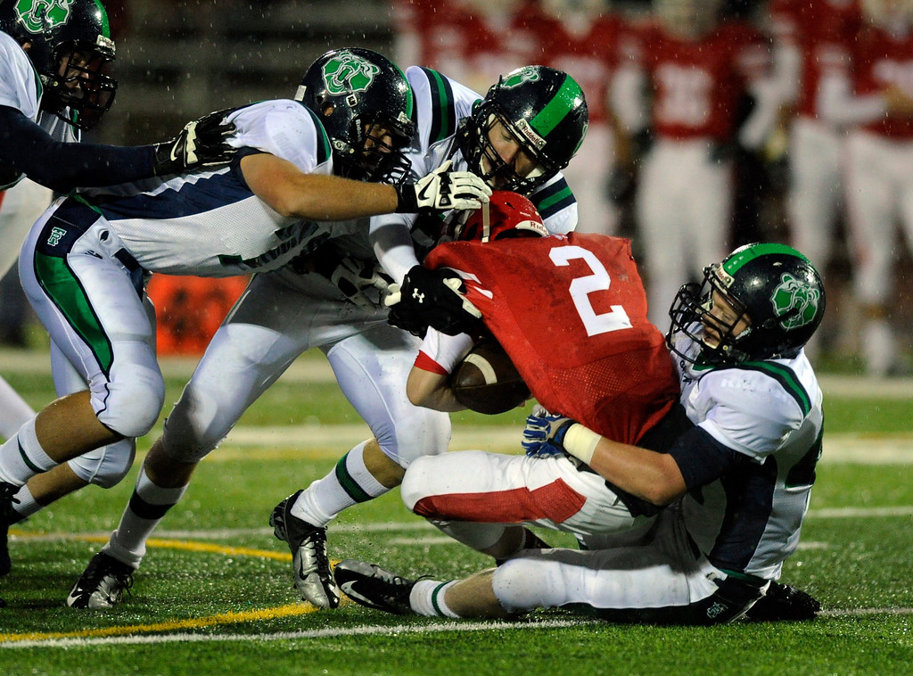 . AURORA, CO. - SEPTEMBER 27: Regis quarterback Matt Houghtaling (2) was brought down at the line of scrimmage by ThunderRidge lineman in the first quarter. The Regis Jesuit High School football team hosted ThunderRidge Friday night, September 27, 2013. Photo By Karl Gehring/The Denver Post