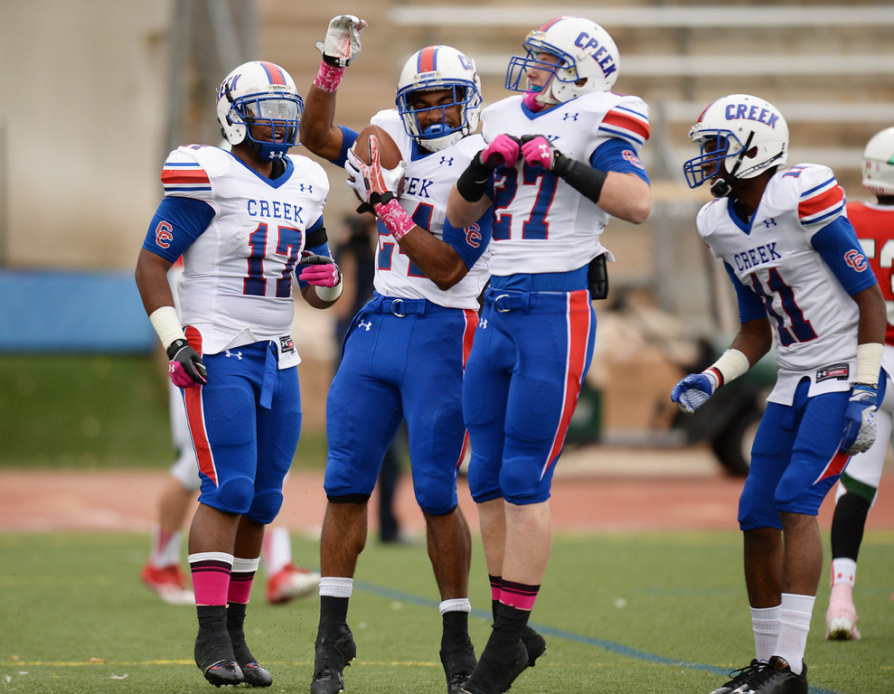 . From left, Patrick O\'Malley (17), Nathan Starks (24), Milkey McCauley (27) and Kris Taylor-Keel (11) of Cherry Creek High School celebrate Stark\'s touchdown in the 1st quarter of the game against Smoky Hill High School at Stutler Bowl. Greenwood Village, Colorado. October 11, 2013. (Photo by Hyoung Chang/The Denver Post)