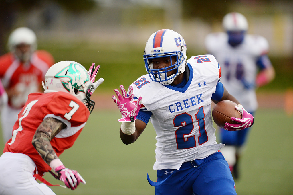 . RB D.J. Luke of Cherry Creek High School (21) controls the ball against Tahir Hopkins of Smoky Hill High School (7) in the 1st quarter of the game at Stutler Bowl. Greenwood Village, Colorado. October 11, 2013. (Photo by Hyoung Chang/The Denver Post)