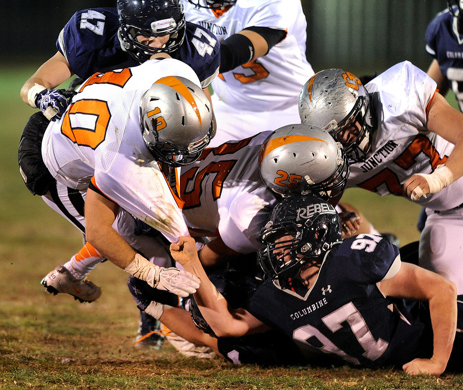 . LAKEWOOD, CO. - NOVEMBER 8: Rebels lineman Garrett Hammers (97) hung on to the jersey of Grand Junction wide receiver Kaleb Johnson (10) to make a tackle in the first half. The Columbine High School football team rolled over Grand Junction 41-6 in a playoff game at Jefferson County Stadium Friday night, November 8, 2013. Photo By Karl Gehring/The Denver Post