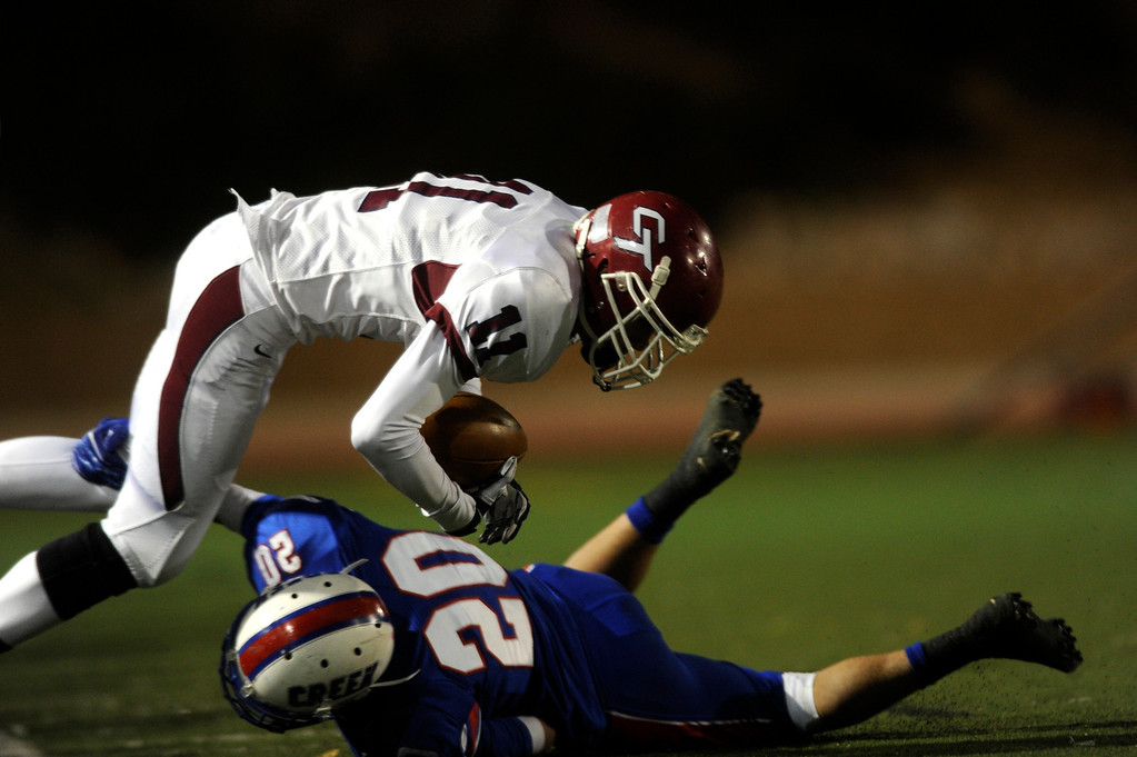. GREENWOOD VILLAGE CO: Nov. 15, 2013  Cherokee Trail player Isaiah Kaiser dives over Aeneas Roberson. Cherry Creek lost 14-27 to Cherokee Trail on Nov. 15, 2013 at Stutler Bowl in Greenwood Village, CO.    (Photo By Erin Hull/The Denver Post)