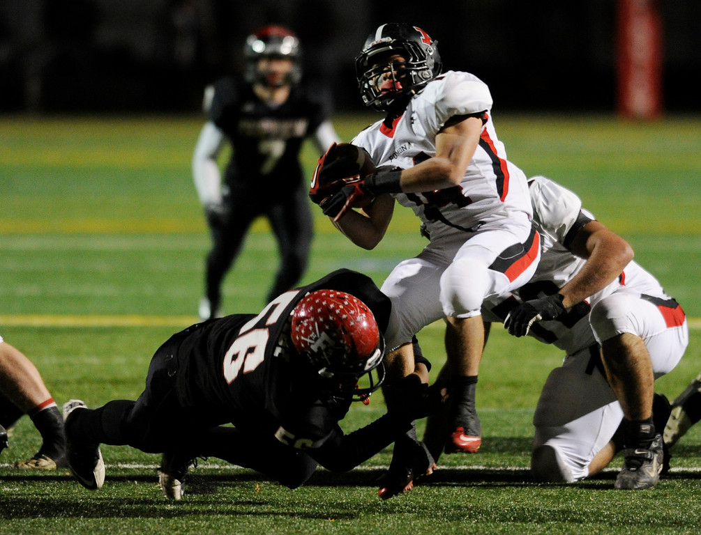 . BOULDER, CO. - NOVEMBER 15: Fairview lineman TJ Kebede (56) caught Pomona running back Chris Marquez (14) by the ankles in the first quarter. The Fairview High School football team hosted Pomona Friday night, November 15, 2003. Photo By Karl Gehring/The Denver Post
