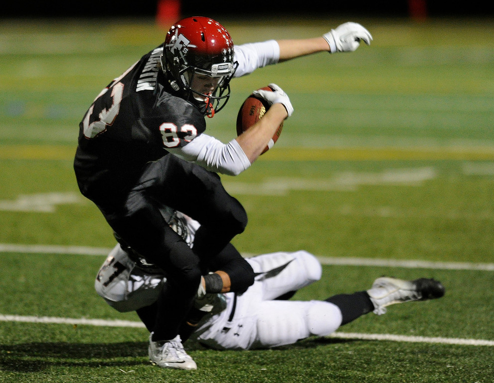 . BOULDER, CO. - NOVEMBER 15: Fairview receiver Sam Martin (83) was brought down by Pomona defensive back Isaac Marquez (27) in the second half. The Fairview High School football team defeated Pomona 35-24 Friday night, November 15, 2013. Photo By Karl Gehring/The Denver Post