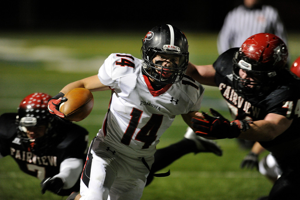 . BOULDER, CO. - NOVEMBER 15: Pomona running back Chris Marquez (14) broke through would be tacklers for a big gain in the first half. The Fairview High School football team hosted Pomona Friday night, November 15, 2003. Photo By Karl Gehring/The Denver Post
