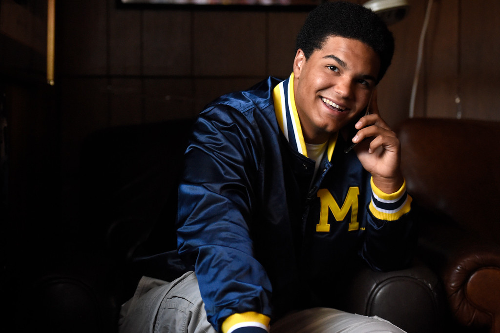 . With a big smile on his face, Carlo Kemp tells Michigan head coach Jim Harbaugh on the phone that he has chosen to go to Michigan for college and to play for the Wolverines at his home in Boulder, Colorado, on November 8, 2015.  The prized defensive lineman had to decide between UCLA, Notre Dame and the University of Colorado at Boulder. Harbaugh said he did a cartwheel upon hearing the news. (Photo by Helen H. Richardson/The Denver Post)