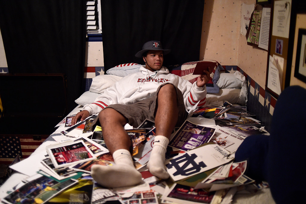 . Carlo Kemp sits atop stacks of recruitment mail on his bed after announcing that he will attend the University of Michigan starting in January on Tuesday, November 11, 2015. (Photo by AAron Ontiveroz/The Denver Post)
