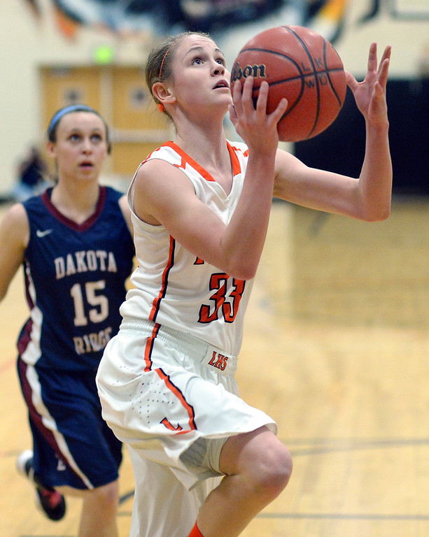 . Lakewood sophomore guard Mackenzie Forrest (33) had a clear path to the basket ahead of Dakota Ridge senior Kendall Fisher (15) in the second half.  Photo By Karl Gehring/The Denver Post