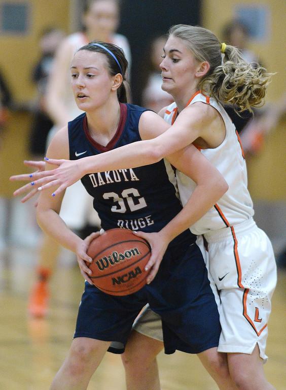 . Dakota Ridge senior Lauren Wood (32) was pressured by Lakewood forward McKenna Bishop (22) in the first half.   Photo By Karl Gehring/The Denver Post