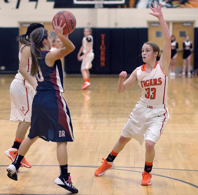 . Dakota Ridge sophomore point guard Caitlin Navratil (10) tried to break the Tigers\' press with a pass past Lakewood sophomore guard Mackenzie Forrest (33) in the first half.   Photo By Karl Gehring/The Denver Post
