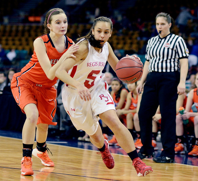 . Regis guard Anna Ptasinksi (5) raced past Lakewood defender Madeleine Coughlin (5) in the first half. The Regis Jesuit High School girl\'s basketball team faced Lakewood in a 5A playoff game Thursday night, March 6, 2014 in Denver, Colorado. (Photo by Karl Gehring/The Denver Post)