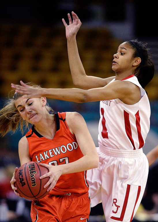 . Regis defender Justine Hall (1) applied pressure to Lakewood junior McKenna Bishop (22) in the first quarter. The Regis Jesuit High School girl\'s basketball team faced Lakewood in a 5A playoff game Thursday night, March 6, 2014 in Denver, Colorado. (Photo by Karl Gehring/The Denver Post)