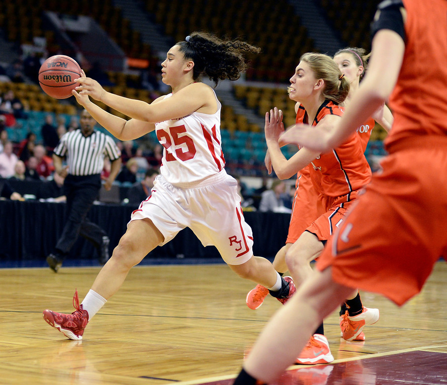 . Regis senior Kelsi Lidge (25) looked for an open teammate in the first quarter. The Regis Jesuit High School girl\'s basketball team faced Lakewood in a 5A playoff game Thursday night, March 6, 2014 in Denver, Colorado. (Photo by Karl Gehring/The Denver Post)