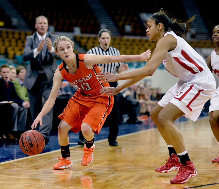. Lakewood guard MacKenzie Forrest (33) looked for a way around Regis defender Justine Hall (1) in the first half. The Regis Jesuit High School girl\'s basketball team faced Lakewood in a 5A playoff game Thursday night, March 6, 2014 in Denver, Colorado. (Photo by Karl Gehring/The Denver Post)