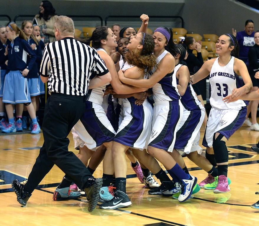 . Mesa Ridge senior guard Tiffani Jackson was surrounded by teammates following her game-winning shot as the Mesa Ridge High School girl\'s basketball team defeated Pueblo South 40-38 in a 4A semifinal game Thursday night, March 13, 2014 in Boulder, Colorado. (Photo by Karl Gehring/The Denver Post)