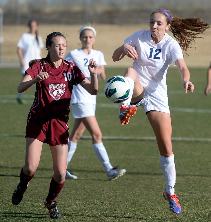 . ARVADA, CO - MARCH 19: Ralston Valley midfielder Sam Bedinger (12) went for the ball in front of Chatfield\'s Erika Chaplin (10) in the second half. The Ralston Valley High School girl\'s soccer team defeated Chatfield 3-2 with an overtime goal by sophomore forward Emma Musson Wednesday evening, March 19, 2014. (Photo by Karl Gehring/The Denver Post)